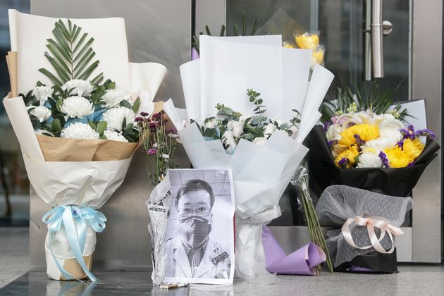 A photo of Li Wenliang is seen with flower bouquets at Wuhan Central