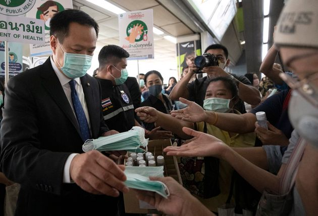 Le ministre de la Santé publique de la Thaïlande, Anutin Charnvirakul, distribuant des masques...