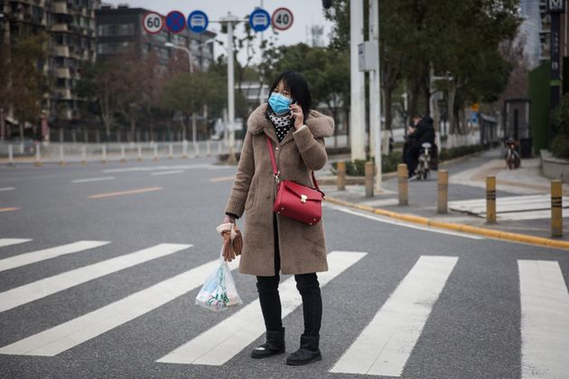 A woman wears a protective mask as she walks in the street on Saturday, Feb. 1, 2020 in
