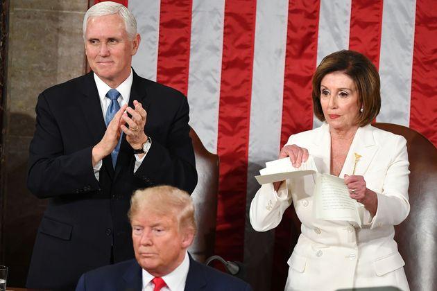 Speaker of the U.S. House of Representatives Nancy Pelosi rips a copy of President Donald Trump's in...