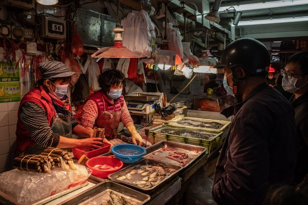 Shoppers wearing face masks purchase seafood at a market on Jan. 28, 2020, in Macau,