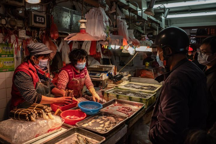 Shoppers wearing face masks purchase seafood at a market on Jan. 28, 2020, in Macau, China.