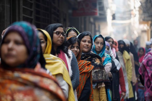 Voters stand in a queue as they wait to cast their vote outside a polling booth during the state assembly...