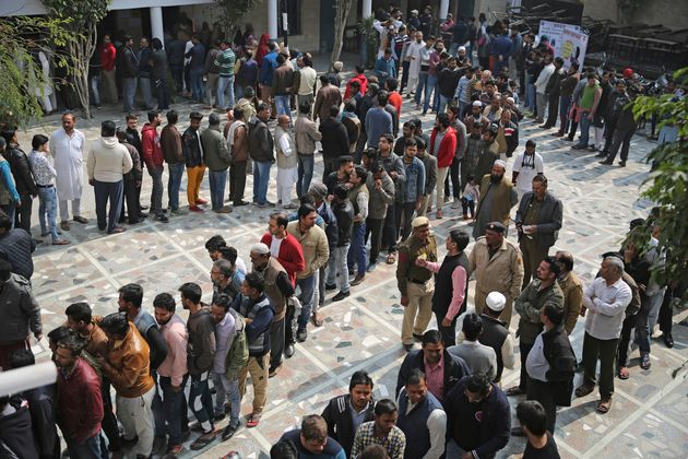 People wait for their turn to cast their vote at a polling station closest to the Shaheen Bagh protest...