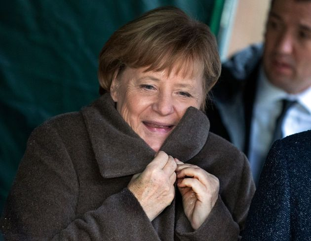German Chancellor Angela Merkel adjusts her coat on a site of the laying of foundation stone for a new...