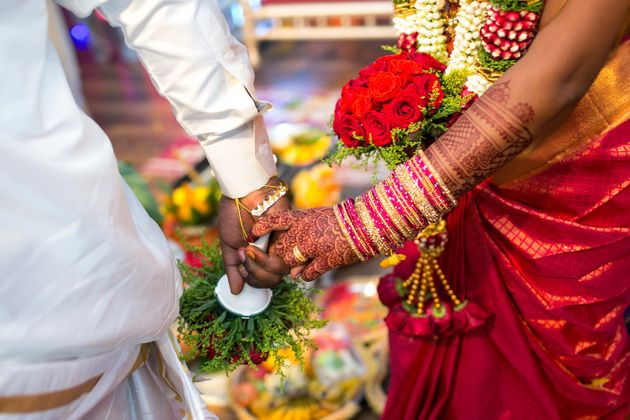 Representational image of a bride and groom performing traditional rituals in