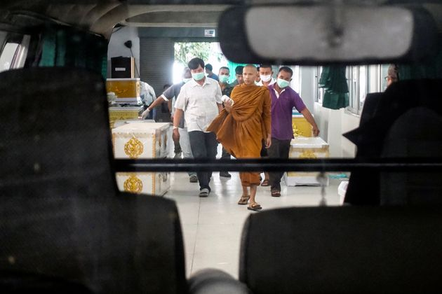 A buddhist monk and rescue workers carry a body of a victim of a gun battle involving a Thai soldier...