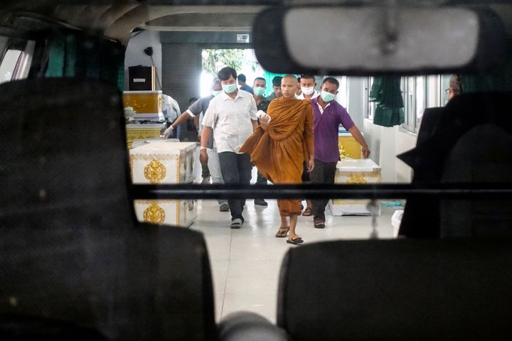 A buddhist monk and rescue workers carry a body of a victim of a gun battle involving a Thai soldier on a shooting rampage at a hospital, in Nakhon Ratchasima, Thailand, February 9, 2020. REUTERS/Athit Perawongmetha