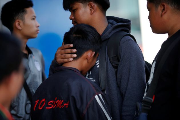 Victim's family members cry in front of the Terminal 21 shopping mall following a gun battle involving...