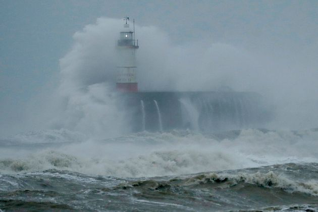 Waves crash over the harbour and a lighthouse in Newhaven on the south coast of