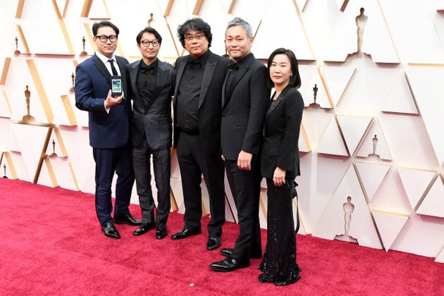 HOLLYWOOD, CALIFORNIA - FEBRUARY 09: Director Bong Joon-ho (C) with cast and crew of