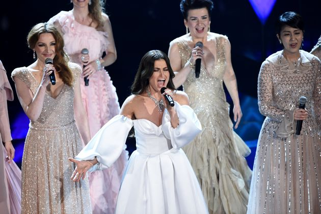 Idina Menzel, center, performs with international voice actresses that play Elsa in the movie