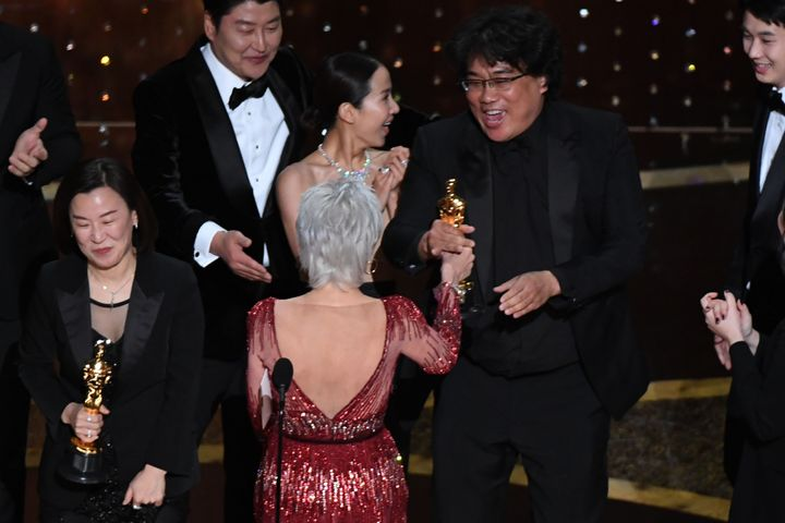 """Kwak Sin-ae and Bong Joon Ho are greeted by Jane Fonda as they accept the award for Best Picture for """"Parasite."""""""