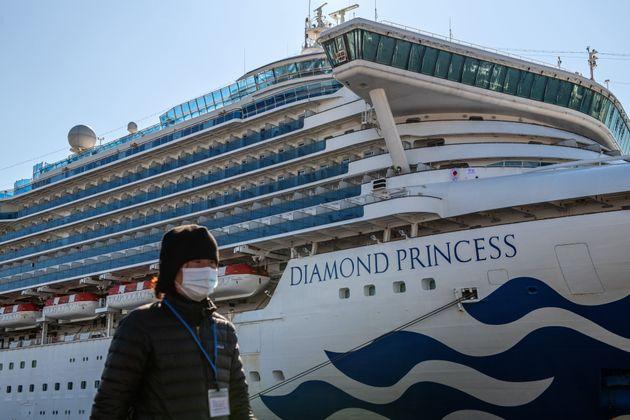 A member of the media wearing a face mask walks past the Diamond Princess cruise ship at Daikoku Pier...