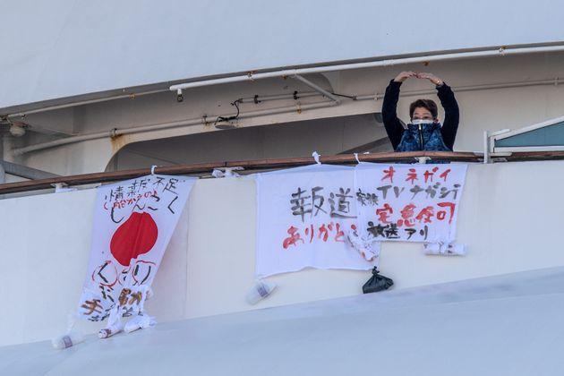 A passenger gestures after hanging a banner reading