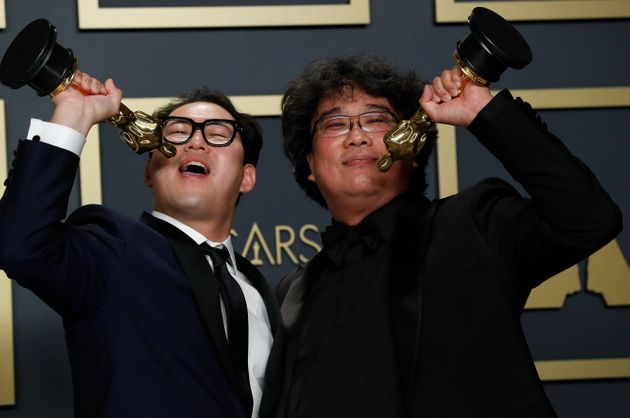 Han Jin Won and Bong Joon Ho pose with the Oscar for Best Original Screenplay for