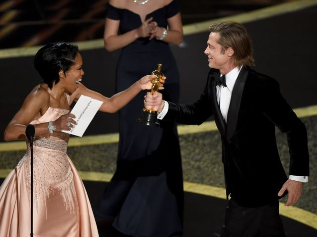 Regina King, left, presents Brad Pitt with the award for best performance by an actor in a supporting role for
