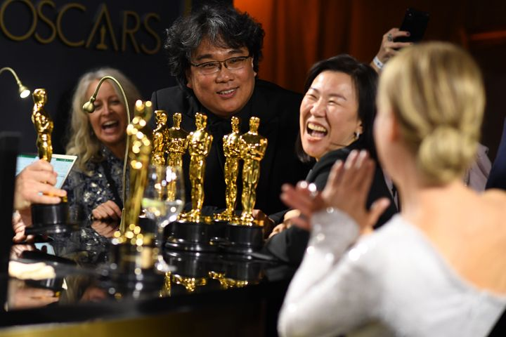 """""""Parasite"""" director Bong Joon Ho, producer Kwak Sin-ae and actor Renee Zellweger wait for their awards to be engraved."""