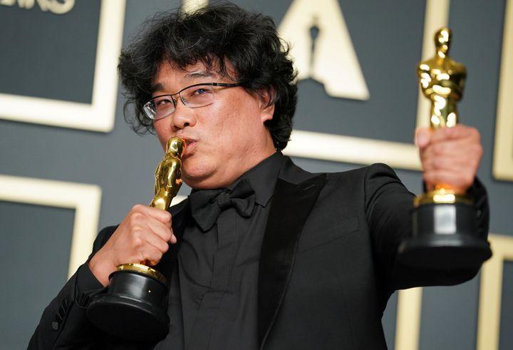 Bong Joon Ho kisses his Oscar trophies.