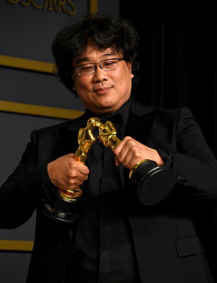 Bong Joon Ho makes his Oscar trophies kiss.