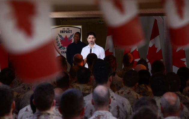 Prime Minister Justin Trudeau and Toronto Raptors president Masai Ujiri address Canadian troops as they...