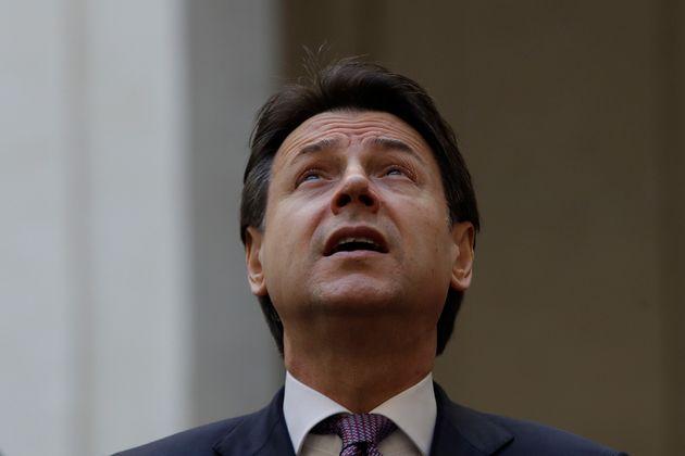 Italian premier Giuseppe Conte looks at the sky as he waits for Albania's Prime Minister Edi Rama at...