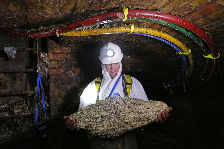 "Tim Henderson, a ""flusher"" or trunk sewer technician holds a ""fatberg"" as he works in the intersection of the Regent Street and Victoria sewer in London on December 11, 2014."