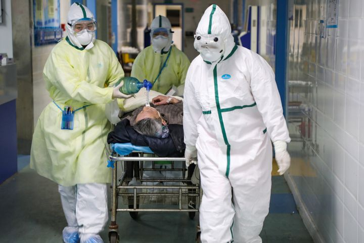 Medical workers in protective suits move a patient in an isolated ward of a Wuhan, China, hospital on Feb. 6, 2020.