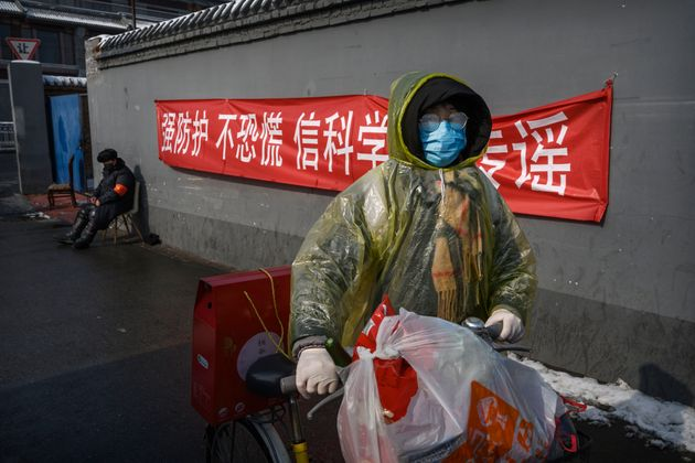 A Chinese woman walks past a sign saying