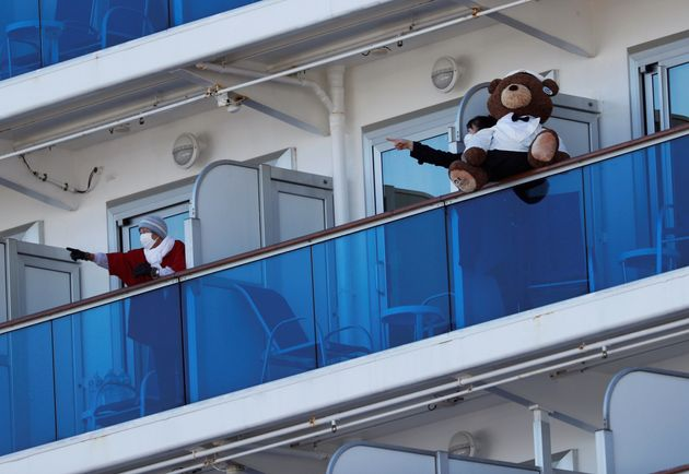 Passengers talk to each other on the balconies of their cabins on the cruise ship Diamond Princess, where...