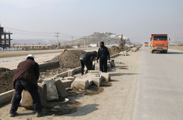 Afghan laborers work on a bridge project funded by the government, in Kabul, Afghanistan, on Feb. 10,