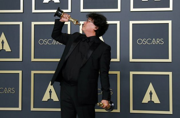 Bong Joon Ho poses with two Oscars, one for Best Director and one for Best International Feature Film...
