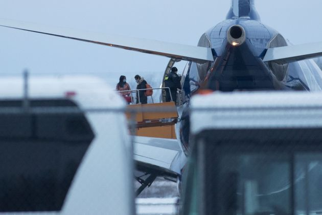Passengers are seen getting off a plane in Trenton, Ont., after travelling from Wuhan, China, on Tuesday....