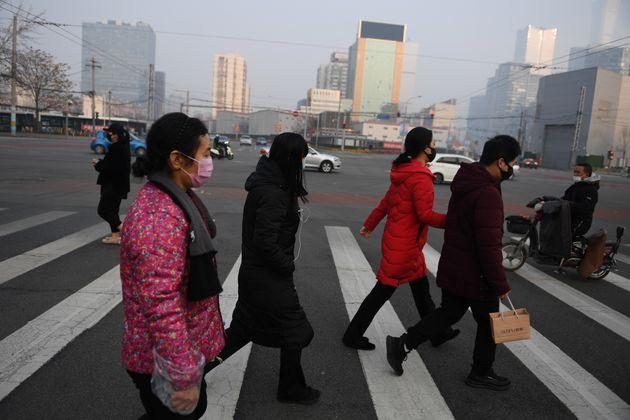 Des personnes traversant une route de Pékin, en Chine, le 11 février 2020 (photo