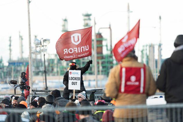 1月21日火曜日、レジーナのCo-op製油所での集会で男性がUnifor旗を掲げています。