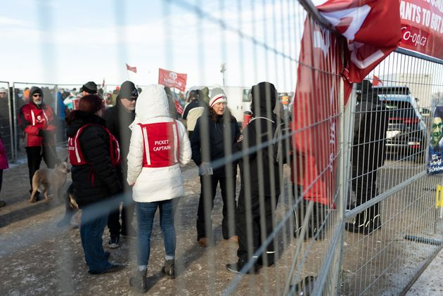 Unifor members stand near a fence at Gate 7 at the Co-op Refinery in Regina on Tuesday Jan. 21,
