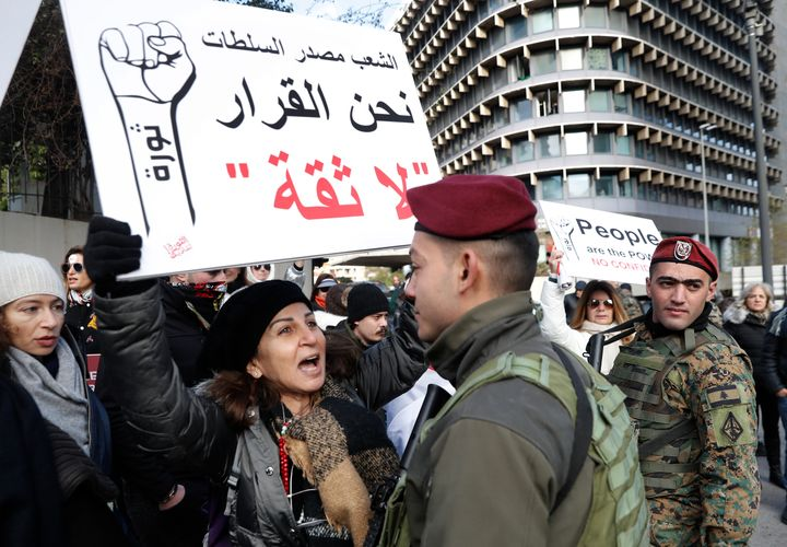 An anti-government protester shouts slogans in front of a Lebanese army soldiers, as she holds an Arabic placard that reads,