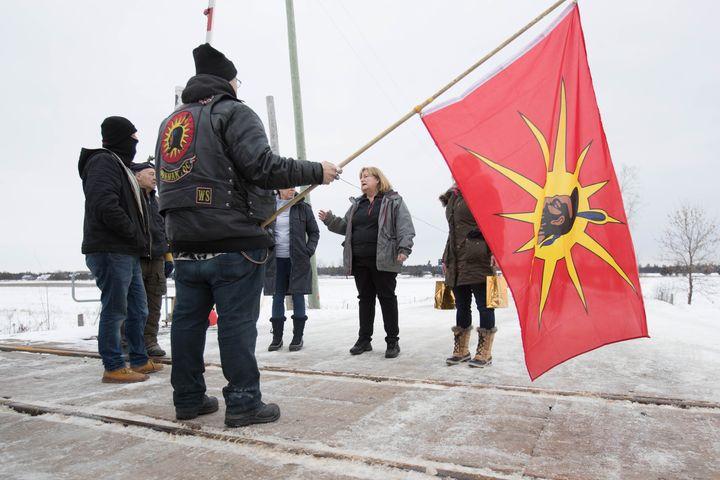 OPP Sgt. Diana Hampson, middle, speaks with members of the Mohawk Territory in Tyendinaga Mohawk Territory, near Belleville, Ont. on Feb. 11, 2020.