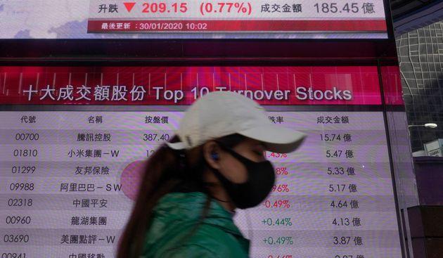 A woman walks past a bank electronic board showing the Hong Kong share index at Hong Kong Stock Exchange...