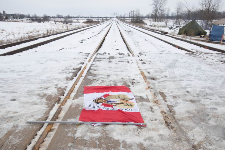 A Canadian maple leaf flag with native symbols on it lays on the train tracks in Tyendinaga Mohawk Territory, near Belleville, Ont., on Tuesday, Feb. 11, 2020.