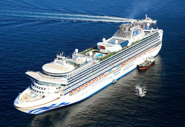 横浜港沖に停泊中の大型クルーズ船ダイヤモンド・プリンセス号と、下船した人を運ぶ海上保安庁の船(右下)=2020年2月5日午前9時、朝日新聞社ヘリから、西畑志朗撮影