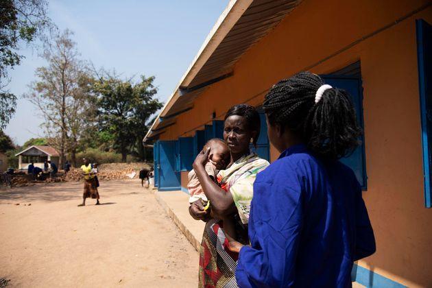 La trabajadora social de Anna, Eunice, sostiene en sus brazos al bebé de Anna en el exterior del