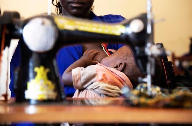 Anna, tras su máquina de coser, da de mamar a su hijo de diez meses. En el centro hay cuidadoras...