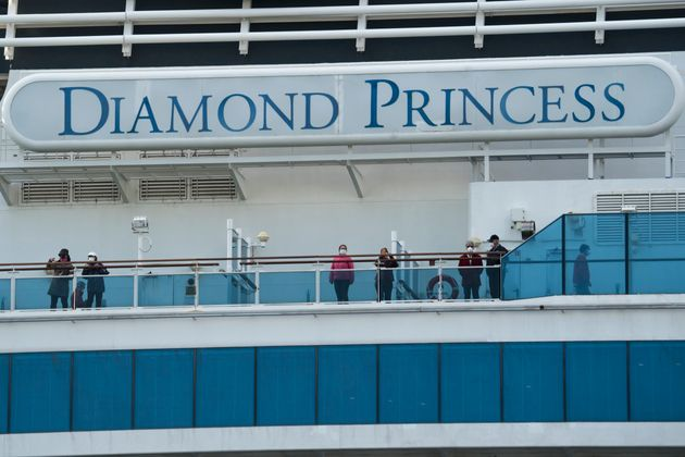 Passengers on board the Diamond Princess cruise ship are seen as the ship arrives at Daikoku Pier where...