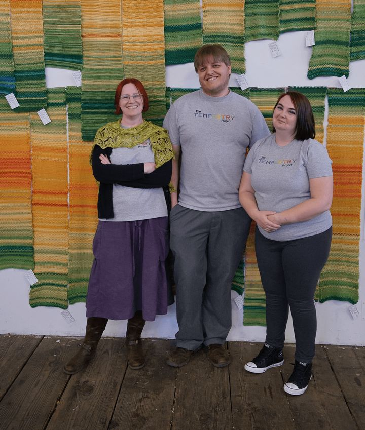 Tempestry Project co-founders Emily McNeil (left), Justin Connelly (centre) and Marissa Connelly (right) display tempestries at Deception Pass, in Washington, U.S.