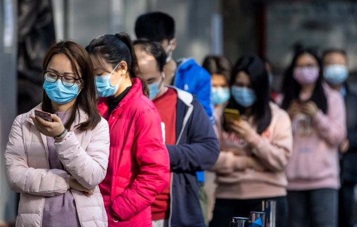 People wait in line outside a pharmacy in Guangzhou, China, on Thursday after winning a lottery to buy protective masks. Senior Chinese officials have been urging workers to return to their jobs amid the coronavirus outbreak.