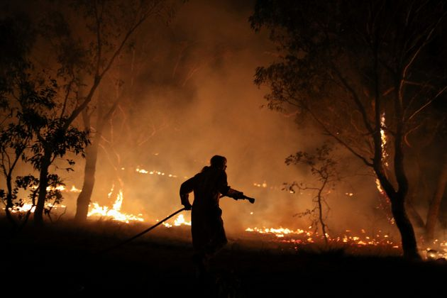 A firefighter from a local brigade works to extinguish flames after a bushfire burnt through the area...