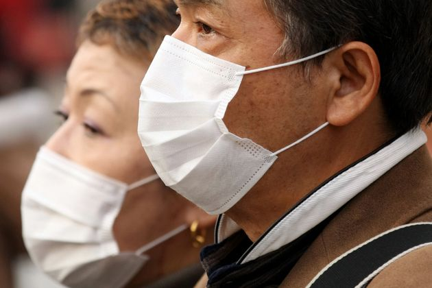 People wearing a mask walks past about the outbreak of coronavirus in Wuhan, China at Ginza shopping...