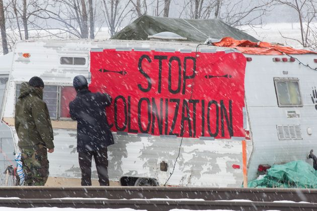 Protesters add a sign to a trailer at the closed train tracks during a rail blockade in Tyendinaga Mohawk...