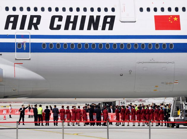 In this May 13, 2019 file photo, airline crew members gather near the underbelly of an Air China passenger...